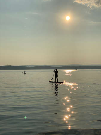 Silhouette of anonymous person rowing on paddle board on rippling surface of sea with sunlight reflections in summer evening