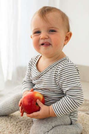 Cute baby girl are sitting with apple white background interior. Funny child explores the fruit Stockfoto - 165038095
