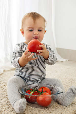 Cute baby girl are sitting whith tomato white background interior. Funny child explores vegetable Stockfoto