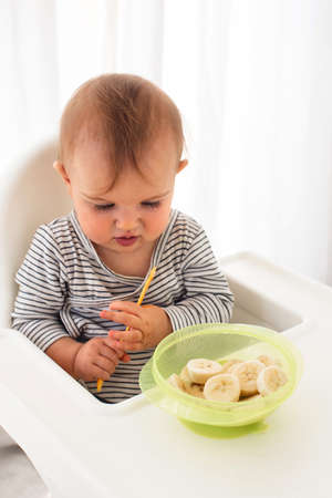 Cute baby girl are sitting whith sliced banana white background interior. Funny child explores the fruit Foto de archivo