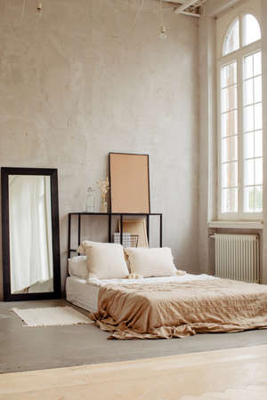 Empty wide bed with soft pillows and cute linens in big room with light windows Stockfoto - 165068982