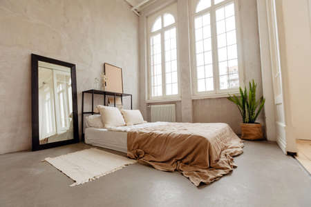 Empty wide bed with soft pillows and cute linens in big room with light windows