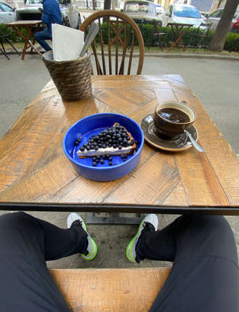 From above of ceramic bowl with slice of cheesecake topped with blueberries and big mug of tea on wooden table