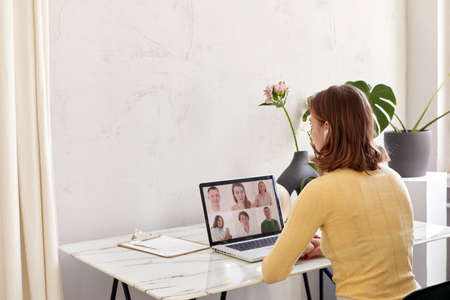Young woman talk on video call on laptop, millennial girl rest sit speak chat with colleagues, have webcam conference, technology concept
