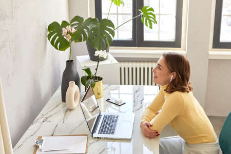 Side view of female in wireless earphones sitting at table with netbook and enjoying music while smiling and looking up