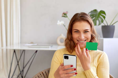 Delighted female with plastic card and smartphone making online purchase while looking at camera at home Foto de archivo