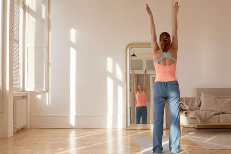 Back view of fit female athlete in sportswear standing in front of mirror at home and stretching raised arms while warming up before workout
