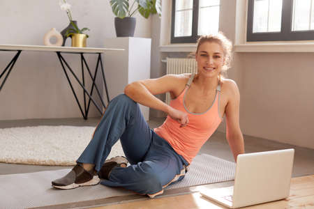Smiling athletic female in sportswear sitting on mat with laptop during online workout at home and looking at camera
