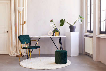 Table with flowers placed in spacious room with chairs in stylish apartment with minimalist interior