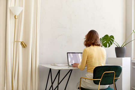 Back view of unrecognizable female in smart casual clothes sitting at desk and browsing data on netbook with empty screen while working in stylish workplace at home Foto de archivo