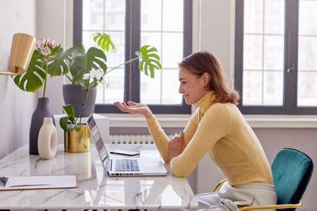 Side view of female in smart casual outfit gesticulating and speaking during online meeting in creative workspace Foto de archivo