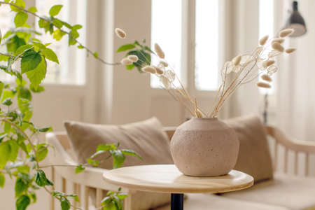Vase with twigs in stylish room