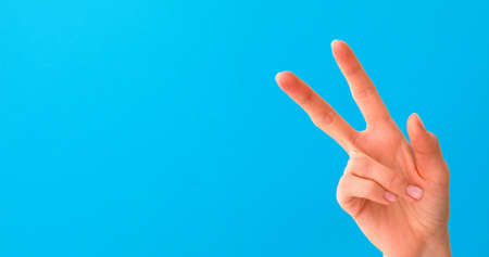 Woman hand doing victory sign isolated on blue