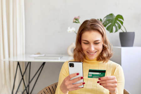 Smiling woman paying by card for online purchase by phone Foto de archivo