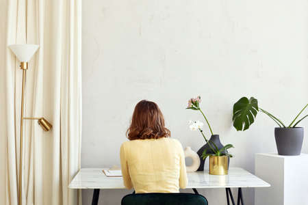 Unrecognizable woman sitting at table with flowers at home