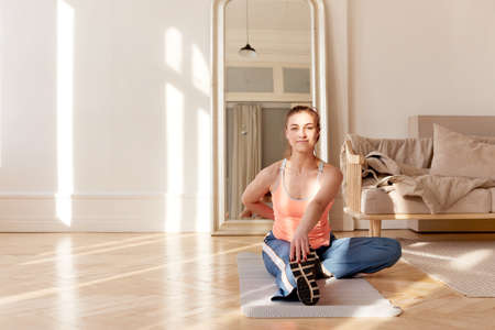 Sportswoman stretching body during training at home
