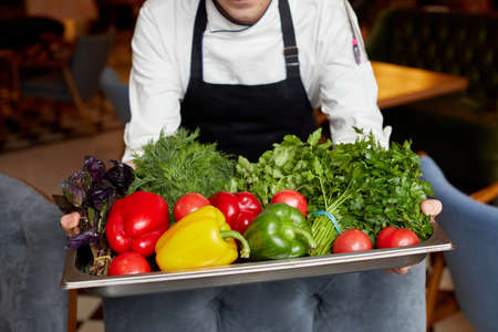 Crop cook with assorted vegetables on tray in restaurant