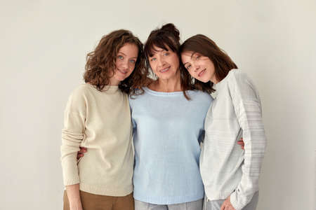Smiling mother hugging daughters and looking at camera