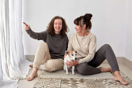 Smiling mother and daughter with dog at home Stockfoto