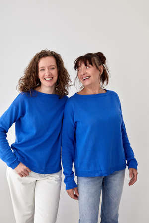 Delighted mother and daughter in similar sweaters in studio Stockfoto