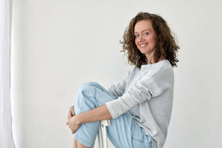 Content stylish woman sitting on chair in studio Stockfoto