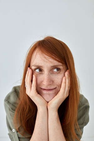Dreamy redhead woman touching face and smiling gently Stockfoto