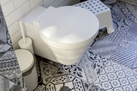 Interior of restroom with toilet bowl and ceramic tile
