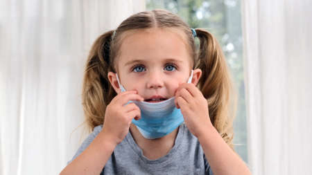 Sick little girl wearing a medical mask against virus closeup looking at camera Stockfoto