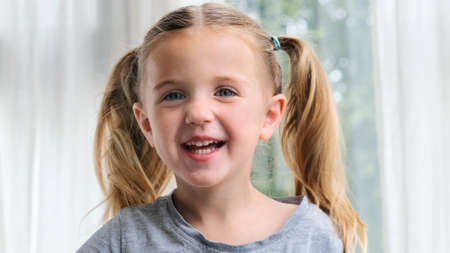 Funny little girl smiling looking at camera at home