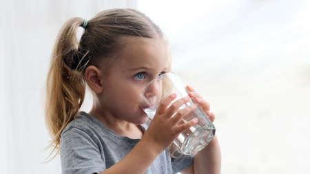 Child girl drinks water silhouette window background