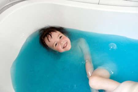 Cute child bathing in blue water in bathtub
