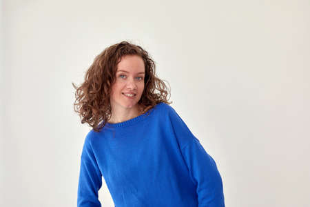 Smiling woman in blue knitted sweater white background