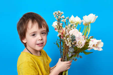 Charming boy with bright blossoming flowers on blue background