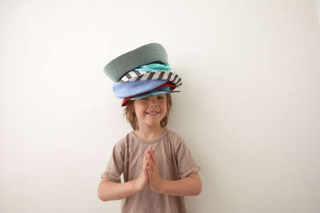 Adorable little boy wearing different hats on head Stockfoto