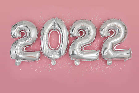 Silver foil balloons numeral 2022 and confetti Flat lay 스톡 콘텐츠