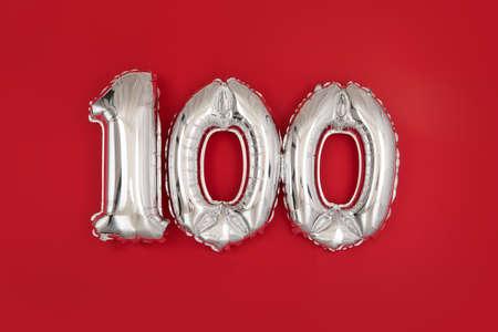Silver 100 balloons on wine red matt background