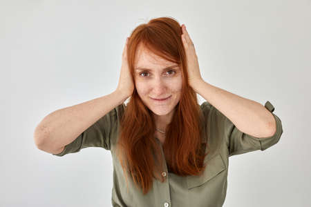 Positive red haired woman covering ears