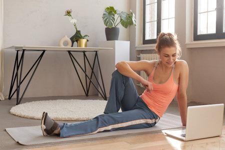 Cheerful sportswoman sitting on mat with laptop 스톡 콘텐츠