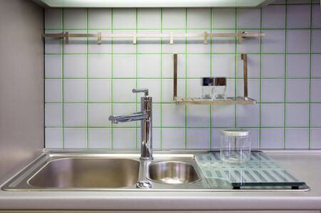 kitchen sink with accessories and ceramic squares on the wall photo
