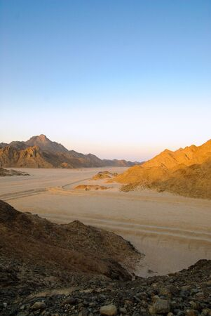 sunset in Egyptian rocky desert yellow mountains and blue sky photo