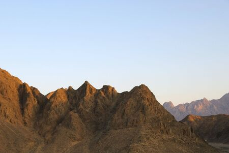 Egyptian rocky desert. mountains sihouette over blue sky photo