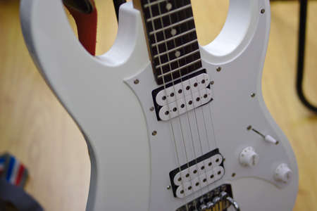 white electric guitar closeup with a switch, two knobs, fret board, wood background