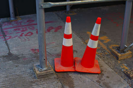 Two orange cones on a sidewalk in a construction zone in the city Banco de Imagens