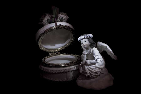 Photo of a figurine of an angel and casket a light brush photo