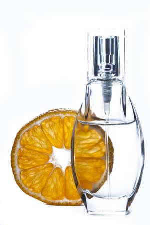 Photo of a bottle of perfume near tangerine