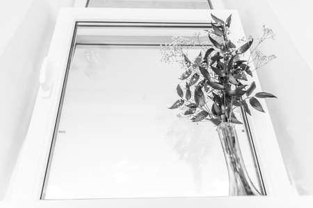 Black-and-white picture of a window with a bouquet on a window sill
