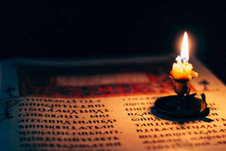 Candle on old ancient orthodox bible reading in the darkness old mysterious religious text Stock Photo