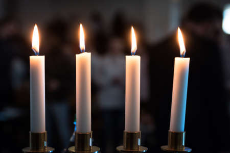 Four candles in dark place with blurry background of people