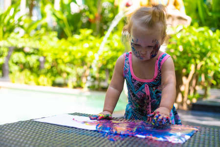 happy baby child draws with colored paints hands.