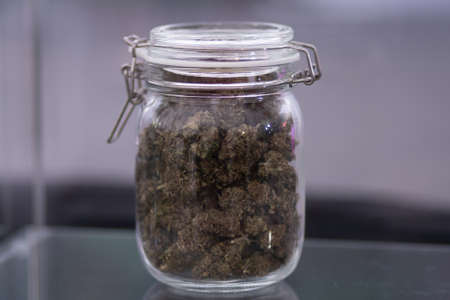 Of flowers of cannabis and scales and joint top view in hand a grinder to grind marijuana weed against a background. In hand a grinder to grind marijuana weed.